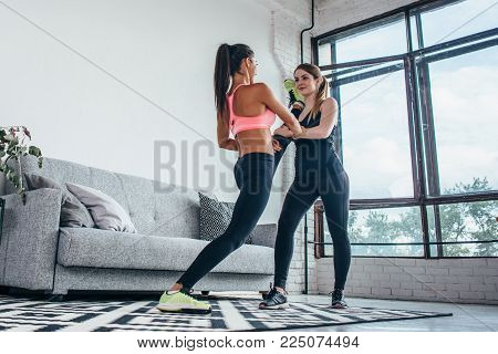Fit girls preparing legs workout. Leg stretching exercise fitness woman doing warm-up, hamstring muscles stretch standing at home