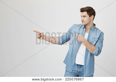 Indoor shot of confident handsome young guy looking and pointing left while standing over gray background. Attractive macho going towards cute girl that sits alone. Hey, wanna have drink or two.