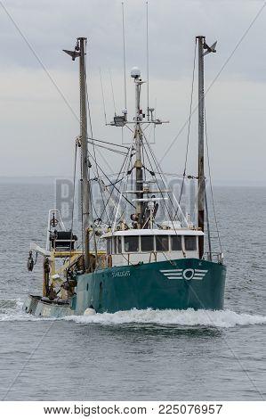 New Bedford, Massachusetts, USA - February 4, 2018: Commercial fishing vessel Starlight, hailing port Boston, Massachusetts, approaching New Bedford on cloudy morning