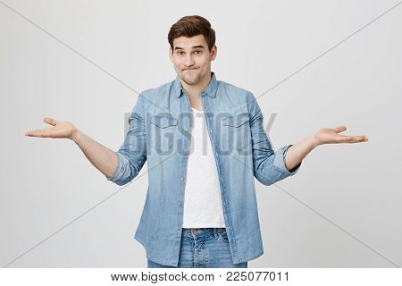 Confused and questioned young guy with stylish haircut, shrugging shoulders while stretching hands in uncertainty gesture, over gray background. Guy do not know what gadget is better.