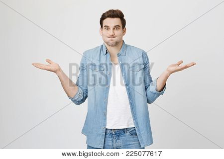 So what, Who cares. Unsure doubtful stylish european dark-haired man wearing denim shirt shrugging his shoulders in questioning gesture of uncertainty and having regretful clueless look