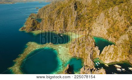 Aerial view: Twin Lagoon with blue, azure water in the middle of small islands and rocks. Beach, tropical island, sea bay and lagoon, mountains with forest, Palawan, Coron. Busuanga. Seascape, tropical landscape. Philippines. Travel concept