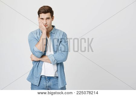 Studio shot of handsome dark-haired man in denim clothes, resting his head on hand, frowning face, being displeased and upset. Face expression and negative emotions