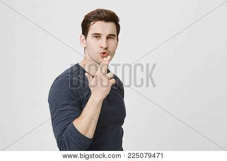 Horizontal portrait of confident young man makes shooting gesture, ready to reach great success, pouting lips. Handsome man makes gun gesture with hands and looks with appeal at camera.