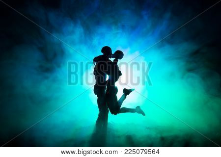 Love Valentine`s Day Concept.sillhouette Of Sweet Young Couple In Love Standing In The Field And Hug