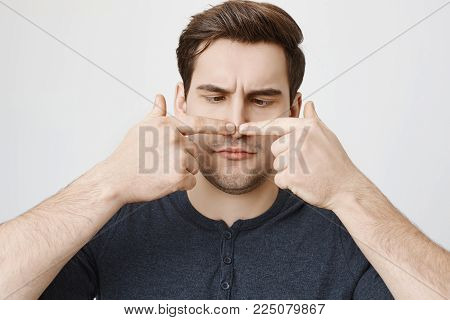 Close-up portrait of funny guy with cute haircut touching his nose with both index fingers and looking at it, standing over gray background. Man is checking if he drank too much.