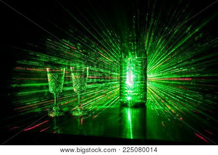 Two Glasses Of Vodka With Bottle On Dark Foggy Club Style Background With Glowing Lights (laser, Sto