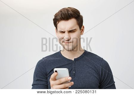 Portrait of attractive athletic caucasian man reading something via smartphone with disbelieving expression, standing over gray background. Son bought new cellphone and do not know how to use it.