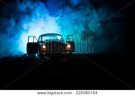 Silhouette Of Old Vintage Car In Dark Foggy Toned Background With Glowing Lights In Low Light, Or Si