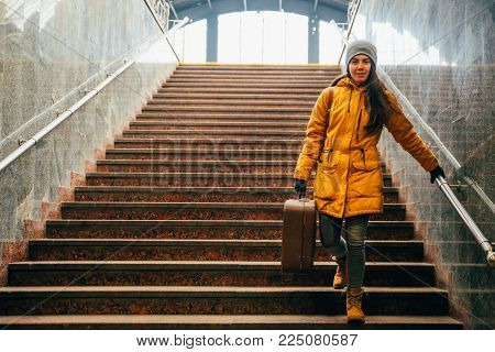 young woman with bags on stairs at railway station