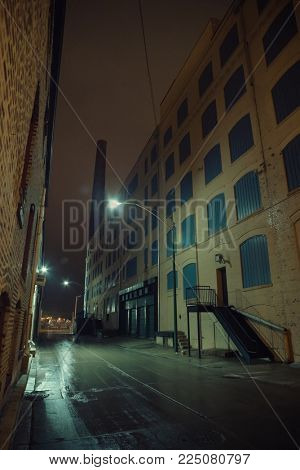 Dark foggy urban city alley at night after a rain with a warehouse and vintage smokestack.