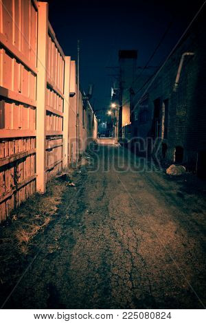 Dark and eerie urban city alley with an old vintage factory warehouse and smokestack at night.