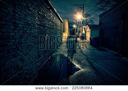 Shadow of a scary man in a dark and eerie urban city alley after a rain at night.