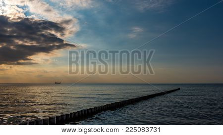 containership as a sillhouette and a groyne with sunbeams