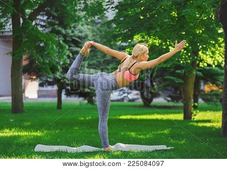 Fitness, woman training yoga in std bow pose outdoors in the park, copy space. Young slim girl makes exercise. Stretching, wellness, calmness, relax, healthy, active lifestyle concept
