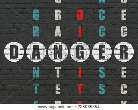 Safety concept: Painted white word Danger in solving Crossword Puzzle