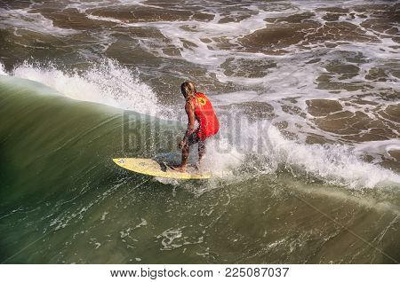 September 30, 2016.  Manhattan Beach, California. A surfer riding the waves at manhattan beach california on the west coast.