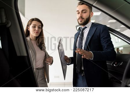 Portrait of handsome car salesman showing luxury car to client in dealership showroom, shot from inside car