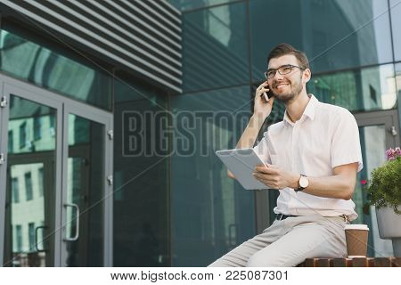 Happy businessman with smartphone and tablet outdoors. Young salesman working with mobile and digital device, sitting at modern building, copy space