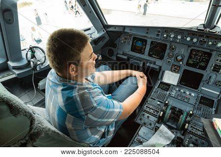 Cayo coco, Cuba,airport, July 20, 2013, great amazing closeup view of young adolescent sitting inside passenger aircraft cockpit and looking ahead