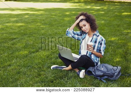 Dreamy black student girl with laptop and coffee outdoors. Smiling woman sitting on grass with computer, surfing the net or preparing for exams. Technology, education and remote working concept