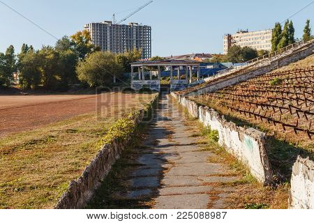 Autumn road on the destroyed stadium against the blue sky and construction of the building.