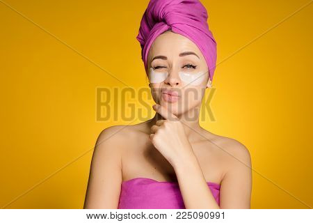 a woman with a towel on her head after showering patches under her eyes