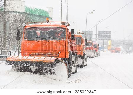 Snowplow trucks removing snow on the road street during blizzard snowstorm in Moscow, Russia