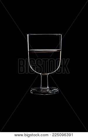 A low glass with white wine isolated on black background.
