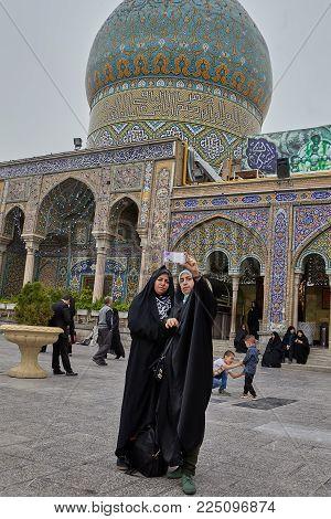 Tehran, Iran - April 27, 2017: Iranian women in hijab take pictures of themselves near the Shrine of Hazrat Abdulazim al-Hasani.