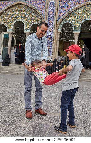 Tehran, Iran - April 27, 2017:Dad with his son and daughter is playing near the Shrine of Hazrat Abdulazim al-Hasani.