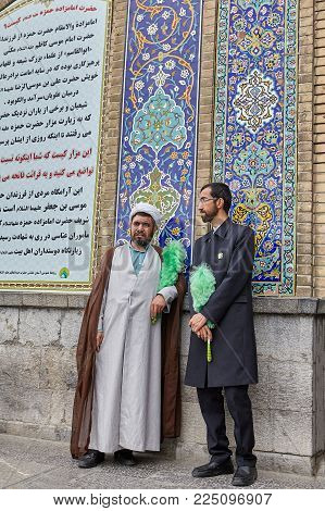 Tehran, Iran - April 27, 2017: Iranian mullah in turban and man stand near The Shah Abdol Azim Shrine.
