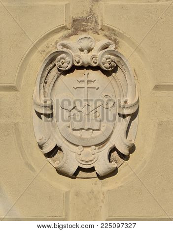 Cross, crosier and mitre, christian religious symbols old relief on a wall in Venice