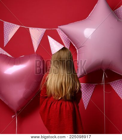 Three years girl toddler kid turned away with pink balloons and flags birthday cap celebrating protest on red background