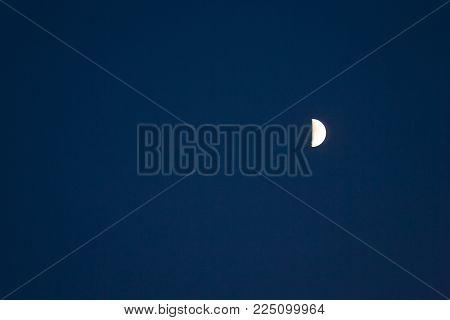 Half moon in dark blue evening sky