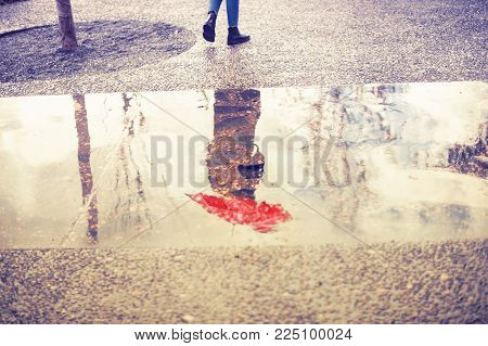 Reflection of a woman in a water puddle walking on side walk red umbrella silhouette