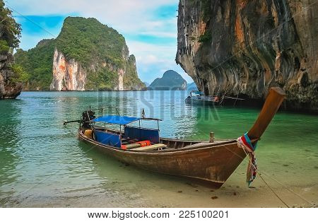 Wooden Boat Boat Moored On A Small Beach In A Beautiful Cove Among The Impressive Karst Formations O