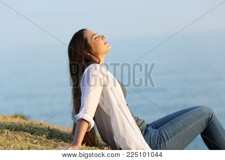 Side view portrait of a relaxed woman breathing fresh air sitting on the grass with the sea and sky in the background