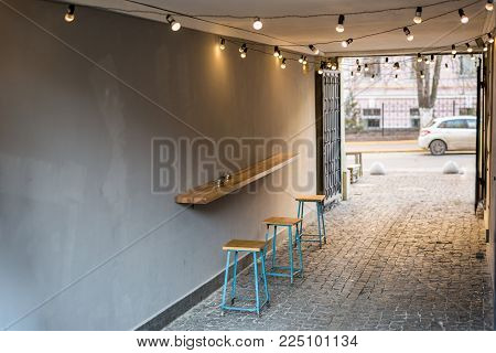 Backyard of old shabby building with one table cafe at the arc passage. Wooden counter and chairs. Place for smoking and coffee.