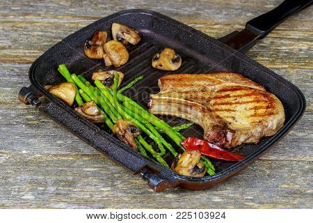 Grilled steak Grilled striploin sliced steak. Juicy thick grilled steak seasoned with rosemary fresh of plate with salt and pepper steak plate with asparagus mushrooms