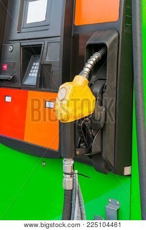 Yellow fuel nozzle at gas station isolated on white background