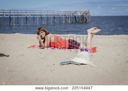 horizontal image of a caucasian woman lying on her stomach on the beach with a wooden pier and the lake in the background on a sunny summer afternoon.