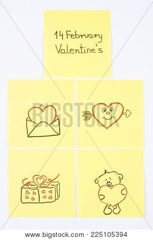 Symbols of Valentines Day on yellow sheet of paper lying on white background, symbol of love