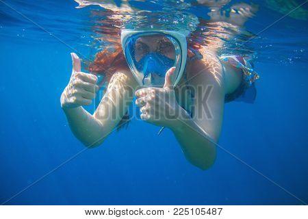 Woman snorkeling mask in blue sea. Snorkeling woman in full face mask. Snorkel show thumbs undersea. Pretty girl in water. Underwater photo shot in ocean. Tropical vacation activity. Water sport