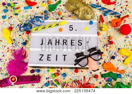 Lightbox with letters - 5. Jahreszeit means HAPPY CARNEVAL - on colorful festive party decoration with steamers, confetti and ballons.