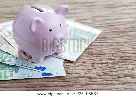 Money savings financial account, Europe economics concept, pink piggy bank on pile of Euro banknotes on wooden table, future growth of compound interest in saving or investing idea.