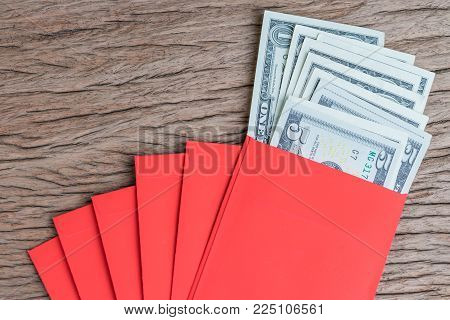 Money in red envelopes Chinese new year greeting gift, pile of US dollar banknotes in red traditional envelopes.