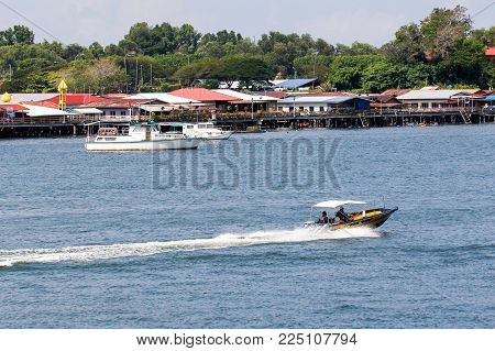 Labuan,Malaysia-Feb 2,2018:Speedboat with background of  Labuan Malay traditional floating village,Patau Patau water village at Labuan island,Malaysia.It's a attraction places in Labuan island among tourists.