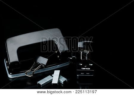 Black stapler, staples, paperclip and punch on dark background with copy space. Office equipment concept