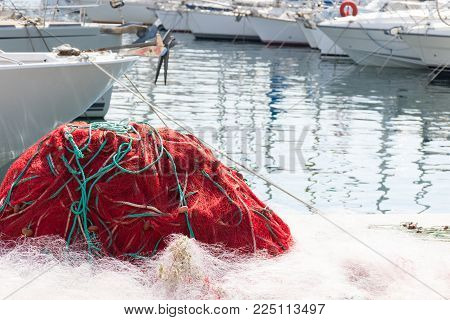 A Tangle Of Red Fishing Net With Aquamarine Rope And White Net With Bows Of Boats In The Background.